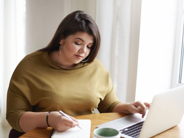 picture-attractive-young-european-female-journalist-wearng-stylish-earrings-knitted-sweater-making-notes-diary-while-working-research-her-new-article-looking-information-online-min