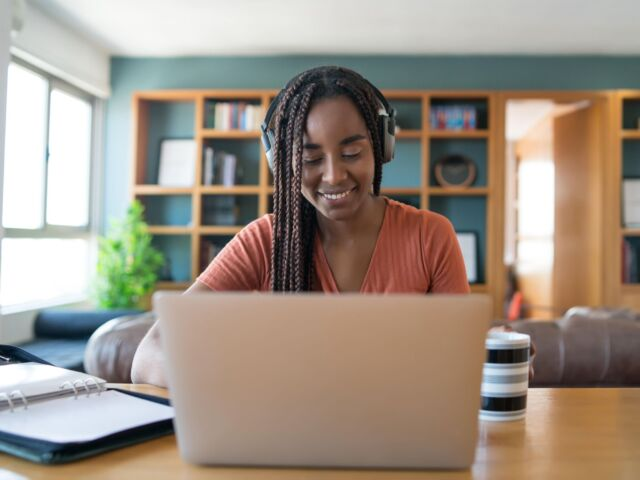 portrait-woman-video-call-with-laptop-headphones-while-working-from-home-concept-min