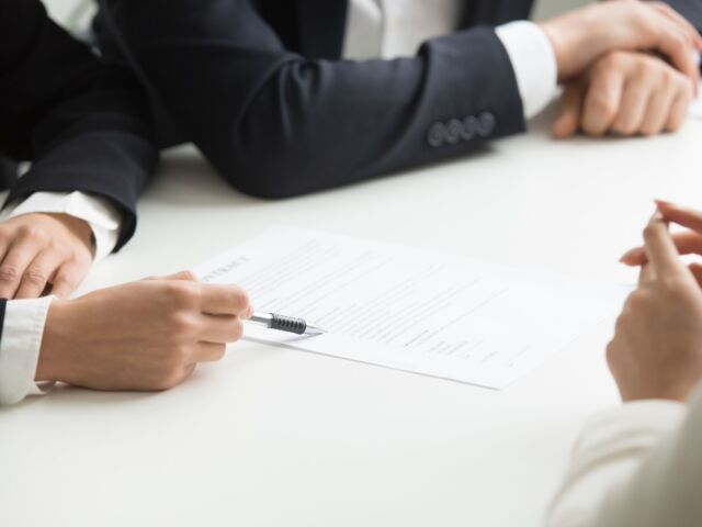 negotiations-about-contract-terms-concept-hand-pointing-document-closeup-min